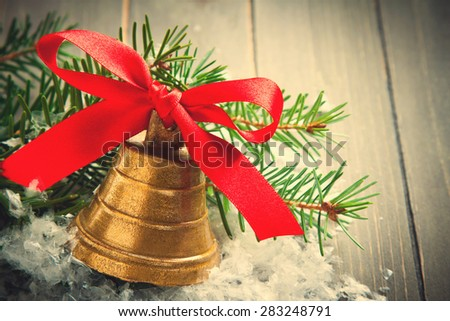 Christmas composition with golden bell with red satin ribbon bow and branch of christmas tree. Christmas background with copy space. Retro style toned. - stock photo