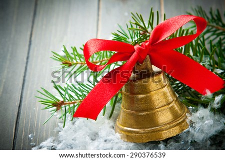 Christmas composition with golden bell with red satin ribbon bow and branch of christmas tree. Christmas background with copy space.  - stock photo