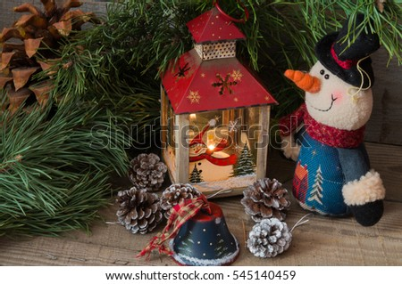 Christmas composition with snowman, fir tree branches, bells, pine cones and Christmas lantern