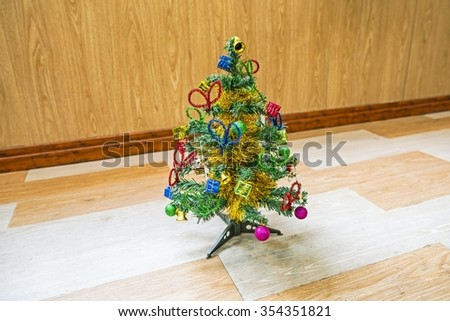 Christmas composition. Xmas tree on wooden floor with gold balls, decorations, toys on branches. Winter holidays card.  - stock photo