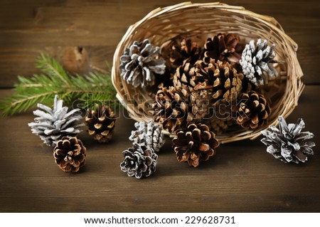 Christmas concept (decoration). Basket  with  cone on rustic wooden background - stock photo