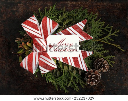 Christmas concept. Fir tree branches, red and white bow, pinecones and tag with the phrase Merry Christmas on brown rustic background. - stock photo