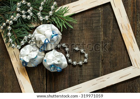 Christmas concept: fresh spruce branches with shiny beads, frame made of birch bark and bags with gifts - stock photo