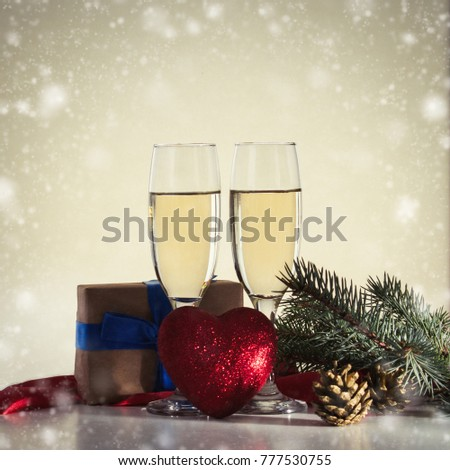 Christmas concept with glasses of champagne and a gift, a red heart, as a symbol of love. Beautiful game of light and shadow.
