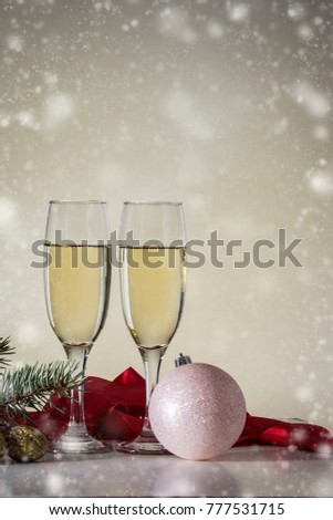 Christmas concept with glasses of champagne and a red ribbon and a white Christmas tree toy.