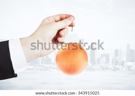 Christmas concept with man hand and red ball - christmas tree toy at city background - stock photo