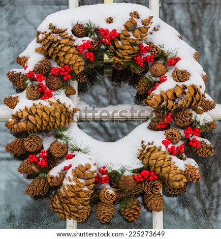 Christmas cone wreath covered in snow - stock photo