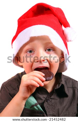 Christmas Cookie A young boy with a christmas hat on eats his cookie. Isolated over white. - stock photo