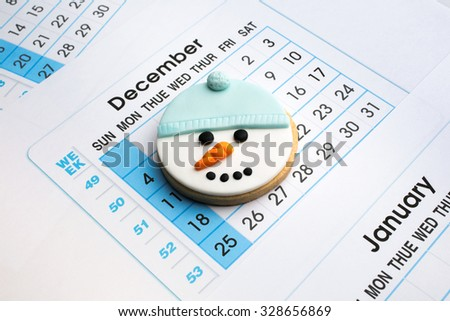 christmas cookie in the shape of a snowman over monthly planner / snowman cookie in calendar december background