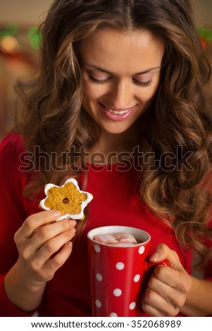 Christmas cookies are wonderful way to enjoy the spirit of the season. Happy young woman having a cup of hot chocolate with marshmallows and cookie - stock photo