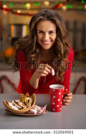 Christmas cookies are wonderful way to enjoy the spirit of the season. Happy young woman having a cup of hot chocolate with marshmallows and Christmas sweets - stock photo