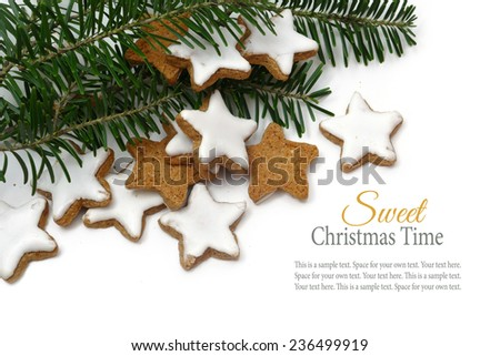 Christmas cookies, cinnamon stars, traditional in Europe called in german zimtsterne, corner background with fir branches on white, sample text in the copy space - stock photo