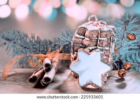Christmas cookies, cinnamon sticks and festive lights, toned image - stock photo