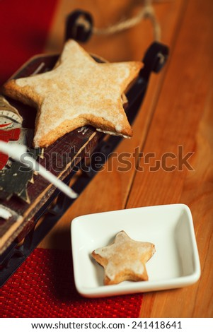 Christmas cookies concept. Creative snack set of cookies with arty handmade decoration - toy sleigh - in vintage cafe. Close up. Indoor shot - stock photo