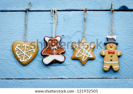 Christmas cookies hanging over wooden background - stock photo