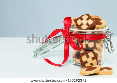 christmas cookies in a glass jar with cookies aside with blueish background - stock photo