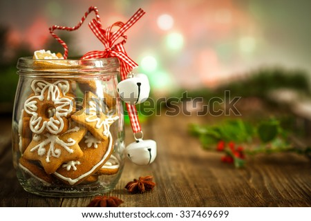 Christmas Cookies in a jar on Wooden background with Christmas Holly - stock photo