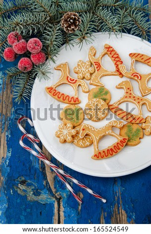 Christmas cookies in festive decor on a white porcelain plate, and blue rustic table decorated with fir branches - stock photo