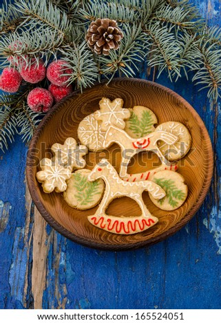 Christmas cookies in festive decor on wooden plate and blue rustic table decorated with fir branches - stock photo