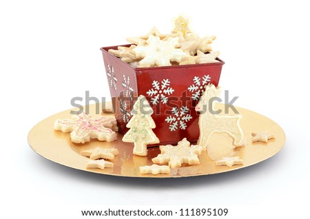 Christmas cookies in red basket on gold plate with white background - stock photo