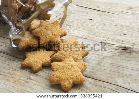Christmas cookies in star shape falling from a cellophane bag on a rustic wooden table, copy space
