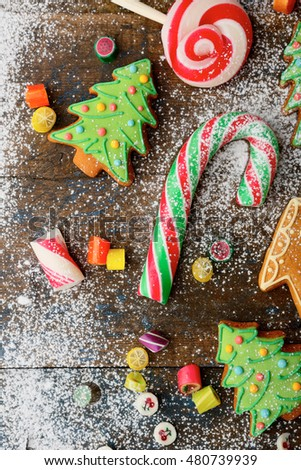 Christmas cookies in the shape of tree, cane and candy strewn with snow on wooden background
