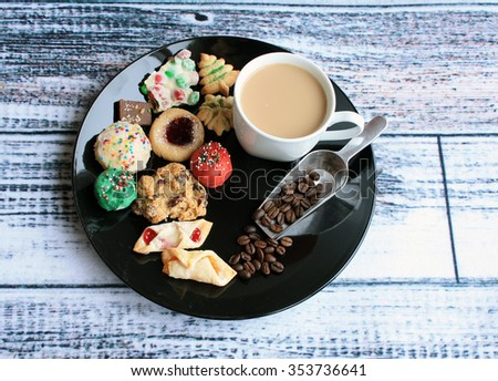 Christmas cookies on a black plate with mug of coffee and shovel with coffee beans on a wooden background/Christmas cookies on plate with coffee/Sugar and Caffeine - stock photo
