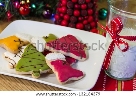 Christmas cookies on a white plate with a glass of milk - stock photo