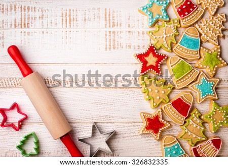 Christmas cookies, rolling pin and cookie cutters on the wooden background. - stock photo