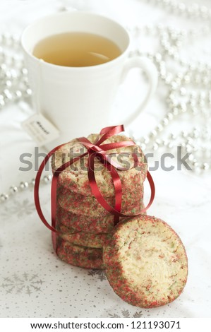 Christmas cookies with a cup of tea in the background