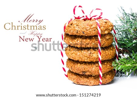 Christmas cookies with festive decoration and pine tree branch and red ribbon isolated  on white background (with easy removable sample text) - stock photo