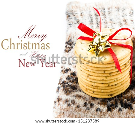 Christmas cookies with red ribbon and knitted mitten as a gift on white background  (with easy removable sample text) - stock photo