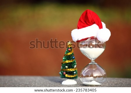 Christmas countdown. Modern Hourglass and Christmas tree -- sand trickling through the bulbs of a crystal sand glass. space on left for text. - stock photo