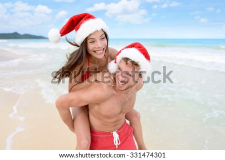 Christmas couple having fun on beach vacation doing piggyback. Laughing funny young friends playing on beach during winter holidays wearing santa hats. Multiracial people - stock photo
