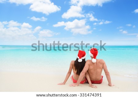 Christmas couple in love lying down relaxing on white sand beach sun tanning in tropical travel destination during winter holidays. Back view of young adults wearing santa hat. - stock photo