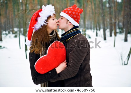 Christmas couple in love with red heart - stock photo