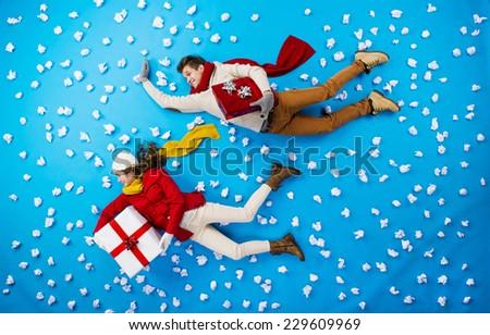 Christmas couple lying on winter background - stock photo