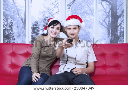 Christmas couple sitting on sofa and watching tv together while the man holds the remote control - stock photo