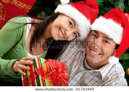 Christmas couple smiling next to a tree with a gift - stock photo