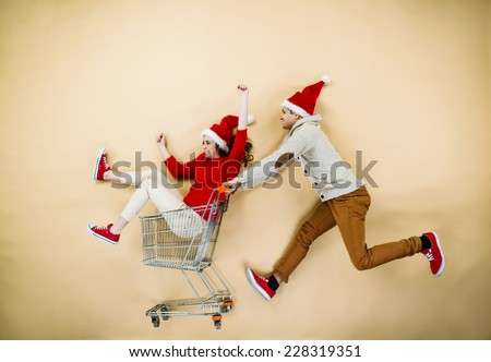 Christmas couple with trolley on beige background  - stock photo