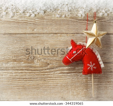 Christmas cowboy background with toy horse and star on wood texture for text - stock photo