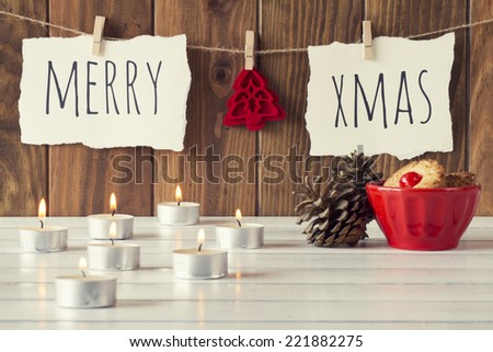 "Christmas cozy scene: candles, two pinecones and a red bowl with some shortbread on a white wooden table. ""Merry xmas"" and a red felt tree is hanging on a rope with clothespins. Vintage Style. - stock photo"