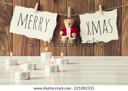 "Christmas cozy scene: some candles on a white wooden table. ""Merry xmas"" and a Teddy bear with Santa Claus dress is hanging on a rope with clothespins. Vintage Style. - stock photo"