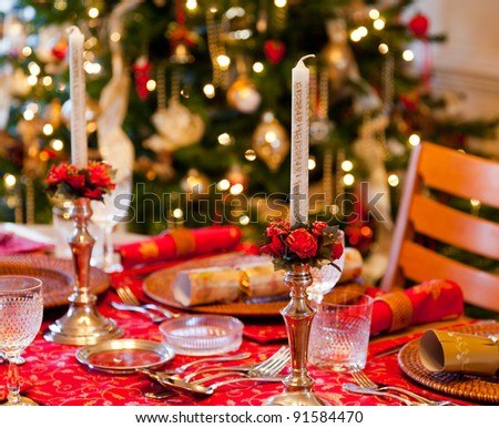 Christmas crackers on table set for Christmas lunch with candles and tree in background