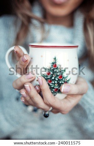 Christmas cup with tree in hands of young woman - stock photo