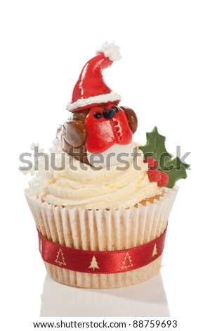 Christmas cupcake decorated with homemade fondant icing robin wearing a santa hat on white background - stock photo