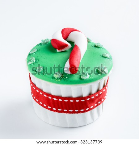 Christmas cupcake in traditional red green colours with candy cane decorative element - stock photo