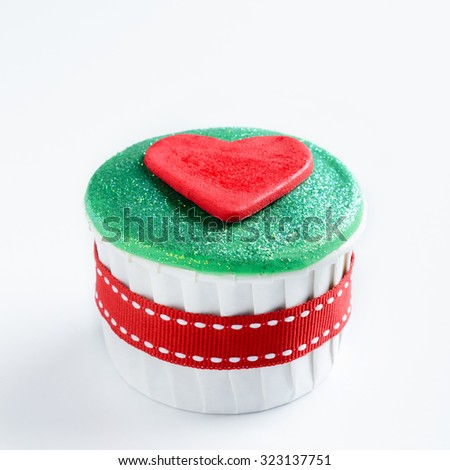 Christmas cupcake in traditional red green colours with heart decorative element - stock photo