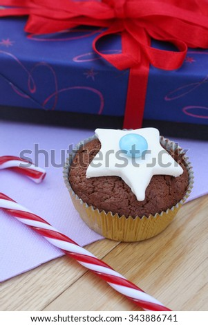 Christmas cupcake  with candy cane and a present on wooden table