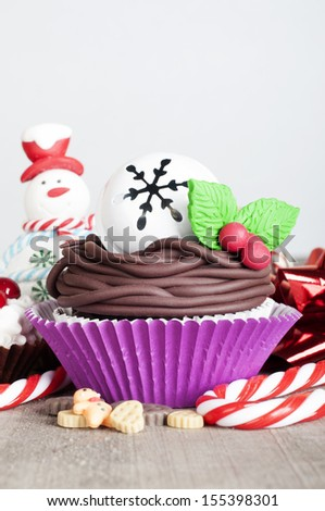 Christmas cupcake with snowman and candy canes - stock photo